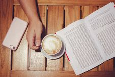 Free Person S Hand Holding White Coffee Mug With Plate On Brown Wooden Board With White And Black Book Stock Image - 109926711