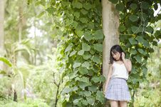 Free Woman In White Spaghetti Strap Top And Gray Skirt Standing In Front Of Tree Royalty Free Stock Photo - 109926935