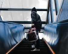 Free Person Wearing Black Hooded Jacket Standing On Escalator While Holding Backpack Stock Photos - 109927033