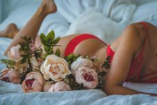 Free Woman In Red Two-piece Bikini Lying On Bed Beside Of White And Pink Roses Royalty Free Stock Images - 109927059