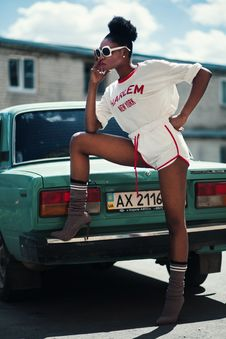 Free Photo Of Woman Wearing White Long-sleeved Shirt And White Dolphin Shorts With Red Trim Standing Near Teal Car Stock Images - 109927064