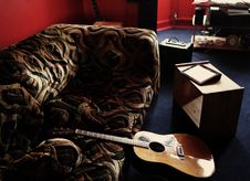 Free Brown Acoustic Guitar Leaning On Brown Velvet Couch Royalty Free Stock Image - 109927066