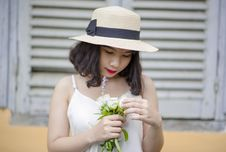 Free Woman Wearing Beige Sun Hat And White Sleeveless Top Holding White Flowers Stock Image - 109927121