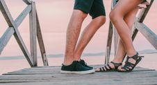 Free Man In Black Low-top Sneakers Leaning Towards Woman In Black Gladiator Flat Sandals On Dock Royalty Free Stock Photos - 109927138
