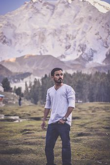 Free Man In Grey V-neck Long-sleeved Shirt With Blue Denim Jeans Behind White Mountain Stock Photography - 109927152