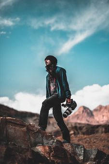 Free Man Wearing Blue Jacket Holding A White And Black Dslr Camera Royalty Free Stock Photography - 109927327
