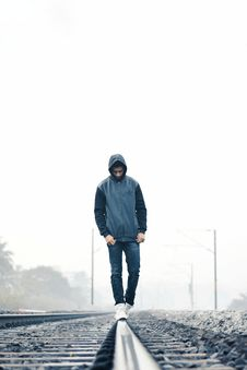 Free Man Wearing Gray And Black Zip-up Hoodie With Black Denim Jeans And White Shoes Walking On Train Railing Behind White Fog Stock Image - 109927641