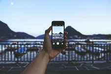Free Person Holding Iphone Taking Picture Of Mountain Near Body Of Water Stock Photos - 109928403