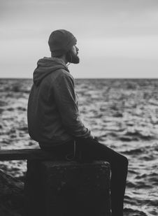 Free Grayscale Photo Of Man In Hoodie And Kit Cap Sitting Near Bodies Of Water Royalty Free Stock Photography - 109928967