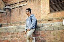 Free Man In Heather-grey Pullover Hoodie And Beige Pants Standing Near Brick Wall Royalty Free Stock Photo - 109929205