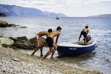 Free Three Men Pushing Speed Boat On Seashore Royalty Free Stock Photo - 109929465