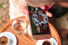 Free Person Holding A Samsung Galaxy Smartphone Taking A Picture On Their Coffees Royalty Free Stock Photos - 110174398