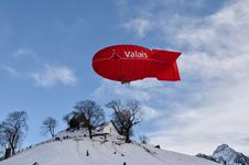 Free Red Valais Blimp Above White Wooden House Stock Image - 110174451