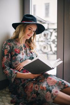 Free Pregnant Woman Wearing Green, Red, And White Floral Dress Reading A Book Near Window Royalty Free Stock Images - 110248559