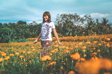 Free Woman In White And Black Floral Crew-neck T-shirt And Red Bottoms Standing On Orange Petaled Flower Field At Daytime Royalty Free Stock Image - 110341966