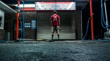 Free Man In Red Shirt And Brown Shorts Standing Near Wall Stock Photography - 110418062