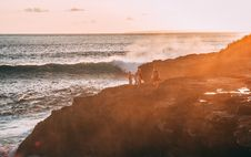 Free People Standing On Cliff Near Body Of Water Golden Hour Photography Stock Photos - 110418153