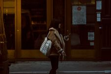 Free Woman Carrying White Tote Standing Beside Brown Glass Door Building Royalty Free Stock Photos - 110501028