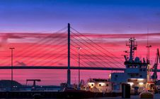 Free Silhouette Of A Bridge Under Red Clouds And Blue Sky Taken During Night Time Stock Photo - 110501040