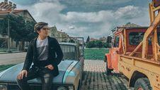 Free Man In Black Zip-up Jacket On Blue Car Beside Orange Truck Stock Image - 110501051