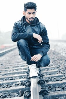 Free Man In Black Leather Zip-up Hoodie And Black Denim Jeans Sitting On Grey Metal Train Railings Surrounded With Rocks During Husky M Royalty Free Stock Photo - 110501065