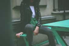 Free Woman Wearing Black Leather Jacket Sitting On Green Wooden Bench Royalty Free Stock Photography - 110501077