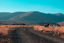 Free Gray Road In Between Brown Grass Field With Mountains Background Stock Images - 110501134