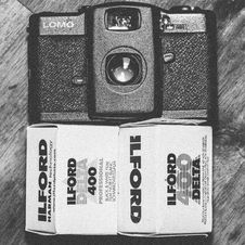 Free Black Lomo Compact Camera Beside Ilford Delta 400 Black & White Film Box Royalty Free Stock Photography - 110521247