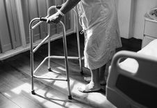 Free Person Holding Medical Walker Beside White Hospital Bed Royalty Free Stock Image - 110654926