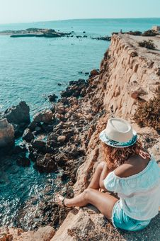 Free Woman Sitting In Stone Near Body Of Water Royalty Free Stock Images - 110655119