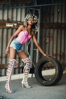 Free Woman Wearing Pink Spaghetti Strap Top And Blue Denim Shorts Holding Vehicle Tire Royalty Free Stock Images - 110655199