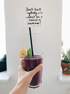 Free Person Holding Clear Drinking Glass With Purple Smoothie With Quotation Decor Royalty Free Stock Photos - 110655218