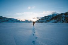 Free Person Walking In Snow Field Near Mountain Cliff Covered With Snow Stock Photos - 110796483