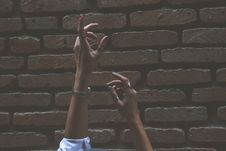 Free Person Raising Its Two Hand Beside Brown Brick Wall Royalty Free Stock Images - 110796489