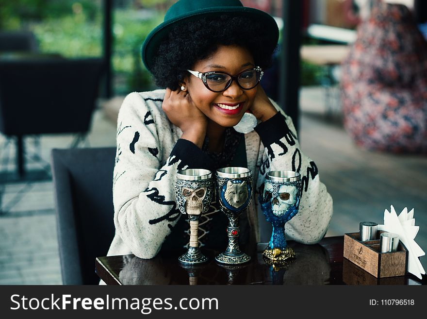 Depth of Field Photography of Woman Leaning Elbow on Table With Three Skull Printed Goblets