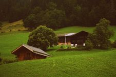 Free Two Brown Wooden Cabins In Green Grass Field Stock Images - 110885694