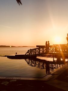 Free Silhouette Of Couple Standing Near Sea Dock At Golden Hour Royalty Free Stock Photos - 110984008