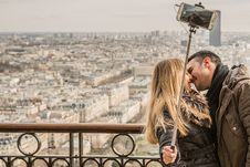 Free Man Kissing Woman Holding Selfie Stick Royalty Free Stock Images - 110984019