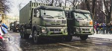 Free Two Green Dump Trucks On Gray Concrete Road Stock Images - 111070134
