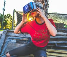Free Woman Wearing Red And Black Top And Blue Distressed Bottoms Wearing Gray And Black Virtual Reality Sunglasses Royalty Free Stock Photography - 111070277
