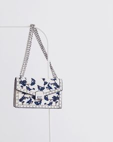 Free White And Blue Floral Flap Sling Bag Hanging On White Steel Rack Royalty Free Stock Image - 111170086