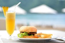 Free Burger With Lettuce And Fries On Plate Beside Pineapple Juice Stock Photography - 111170332
