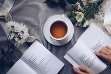 Free White Ceramic Teacup With Saucer Near Two Books Above Gray Floral Textile Royalty Free Stock Photography - 111217157