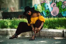 Free Woman Wearing Yellow Off-shoulder Top And Black Pants Sitting On Sidewalk Fixing Lace Sandals Royalty Free Stock Photo - 111217225