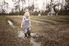 Free Toddler Wearing Blue Denim Overall Pants Walking On Wet Withered Grass Stock Image - 111217251