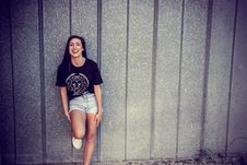 Free Woman Wearing Black And White Crew-neck T-shirt And Gray Denim Short Shorts Outfit Leaning On Gray Wall Stock Image - 111277611