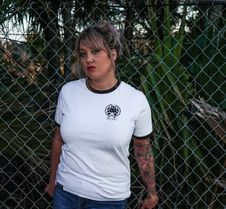 Free Female Wearing Black And White Crew-neck T-shirt And Blue Denim Bottoms Leaning On Chicken Wire Royalty Free Stock Image - 111364536