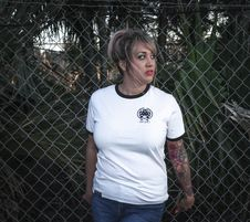 Free Woman Wearing White Crew-neck T-shirt With Black Trim And Blue Denim Bottoms Beside Wire Fence Royalty Free Stock Photo - 111364555