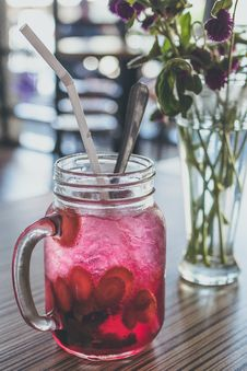 Free Red Beverage-filled Clear Glass Mason Mug With Straw Beside Purple Flowers In Vase Royalty Free Stock Photo - 111364665