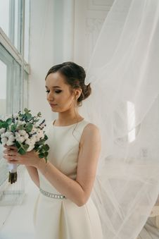 Free Woman In White Sleeveless Gown Holding White Flower Bouquet Infront Of Window Royalty Free Stock Images - 111364709